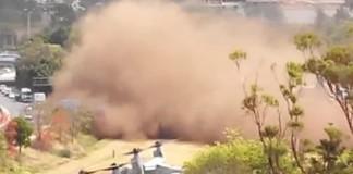 Un hélicoptère soulève un nuage de poussière