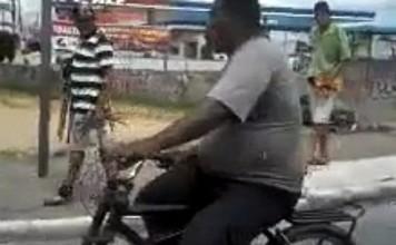 cycliste avec une bouteille de gaz en équilibre sur la tête